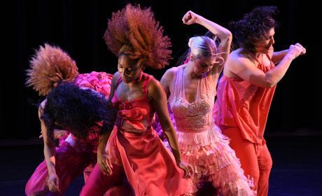 Dancers onstage in top lighting all dressed in various reds