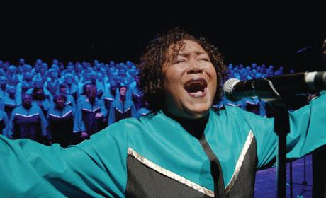 Woman singing with chorus behind her