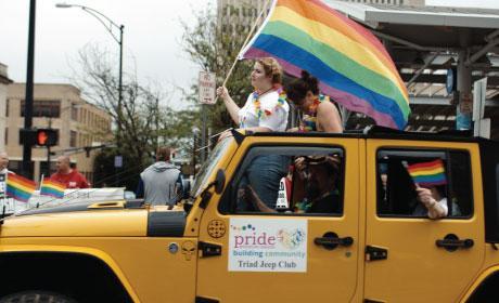 Woman holding a pride flag at parade